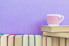 Много различных книг на фиолетовых стене и чашке чаю Стоковые Фото
