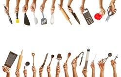 Много рук держа различные инструменты кухни Стоковое Изображение RF