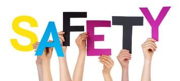 Много рук людей держа красочную безопасность слова Стоковые Изображения RF