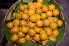Много свежих и красивых апельсинов с хорошим вкусом в корзине на рынке Много оранжевых положенных дальше полок в рынке стоковые фото
