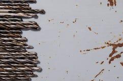 Много сверла на покрашенной предпосылке металла Стоковое Фото