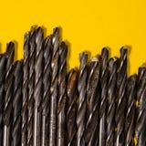 Много сверла на яркой желтой предпосылке Квадратный взгляд Стоковая Фотография