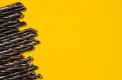 Много сверла на яркой желтой предпосылке Стоковые Изображения RF