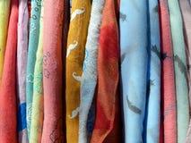 Много светлые шарфы других цветов красных, желтый, оранжевый, голубой, зеленый на вешалке стоковое изображение rf