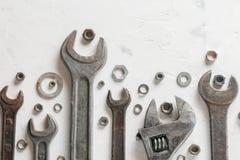 Много старые wrenchs на светлой каменной предпосылке Гайки и шайбы различных размеров Стоковое Изображение RF