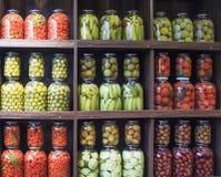 Много стеклянных бутылок с сохраненной едой в деревянном шкафе стоковое фото rf