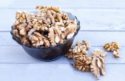 Много стерженей грецкого ореха в стеклянном шаре на деревянной предпосылке сер-голубого цвета Стоковые Фотографии RF