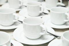 Много строк белых керамических чашки и поддонника с чайной ложкой Стоковое фото RF