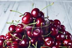Много сладостная вишня и прозрачное стекло на белой таблице Стоковое Фото