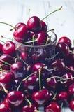 Много сладостная вишня и прозрачное стекло на белой таблице Стоковая Фотография