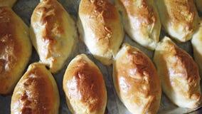 Много традиционных очень вкусных испеченных pasties на подносе от печи в пекарне акции видеоматериалы
