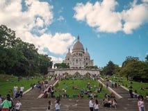 Много туристы и граждане на горном склоне Montmartre на предпосылке Sacre-Coeur стоковые фотографии rf