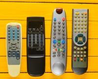 Много устарелых remotes ТВ на желтом деревенском деревянном столе Взгляд сверху стоковое изображение