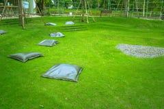 Много черная установка подушки на зеленой траве на открытом саде для отдыхать Стоковые Фотографии RF