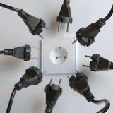 Много черных электрических штепсельных вилок воюют для силы от стенной розетки Стоковые Изображения