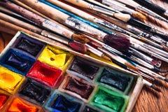 Много щеток и краска для красить на деревянной предпосылке Стоковое Изображение