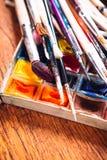Много щеток и краска для красить на деревянной предпосылке Стоковая Фотография RF