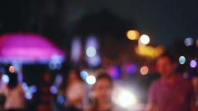 Много люди на ноче выходят светлую предпосылку вышед на рынок на рынок запачканную Bokeh 1920x1080 видеоматериал
