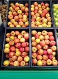 Много яблок плодоовощей красных желтых лежа в коробках в супермаркете Стоковые Фотографии RF