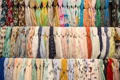 Много ярких женских шарфов и шаль Красочные шарфы вися в рынке Одежды кладут на полку с выбором шарфов или шарфов стоковое изображение rf