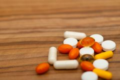 Много ярких таблеток медицины на деревянной предпосылке стоковые фото