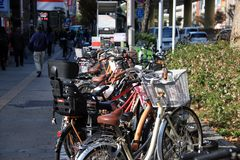 Много bicycle парк на автостоянке велосипеда на тротуаре около дороги на Namba, Японии стоковое изображение