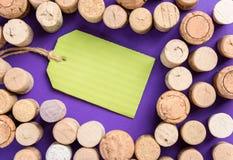 Много cork затворы с зеленым ярлыком на фиолетовой предпосылке Стоковые Изображения RF