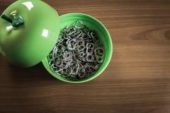 Много metal кольцо вытягивают внутри зеленую пластичную чашку Стоковое Фото