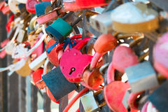 Много padlocks символа влюбленности замужества прикованных на мосте в Астрахани России Стоковая Фотография