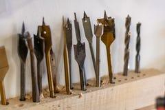 Множественная бронза, сталь, железные лезвия и пункты готовые для того чтобы отрезать и просверлить деревянные планки стоковые фотографии rf