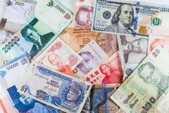 Множественные банкноты валют как красочная предпосылка Стоковые Фотографии RF