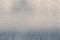 Множественные падения воды или дождевые капли различных размеров на стекле окна Стоковое фото RF