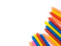 Множественные свечи дня рождения цвета на белой обнаруженной местонахождение предпосылке Стоковые Изображения