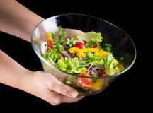 Множество влажных отрезанных овощей в стеклянном блюде на руках женщины стоковая фотография