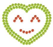 Множество красных и зеленых пилюлек сформировало в форме сердца с счастливым знаком стороны внутрь Стоковая Фотография RF