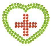 Множество красных и зеленых пилюлек сформировало в форме сердца с добавочным знаком внутрь Стоковое фото RF