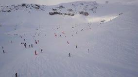 Множество людей катается на лыжах на холме покрытом снегом при подъемы лыжи бежать над ими сток-видео
