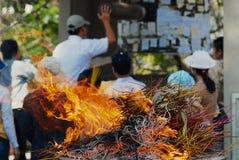Множество ручек ладана горит во время религиозной церемонии с моля людьми на предпосылке в Хо Ши Мин, Вьетнаме Стоковое Изображение