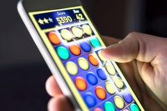 Мобильная игра в экране смартфона Молодой человек играя игру головоломки в приложении телефона Gamer имея потеху Игра цифров, раз стоковая фотография rf