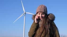 Мобильная телефонная связь, счастливая девушка говоря на сотовом телефоне около турбин энергии ветра видеоматериал