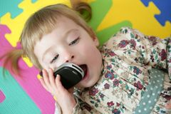 мобильного телефона девушки клетки малыш смешного говоря стоковые фото
