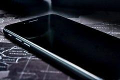 Мобильное устройство сидя на карте мира с экраном  стоковое изображение rf