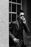 мобильный телефон бизнесмена говорит детенышам Стоковая Фотография