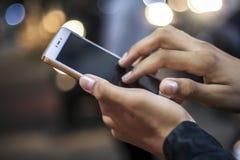 Мобильный телефон в руке на ноче Стоковое Фото