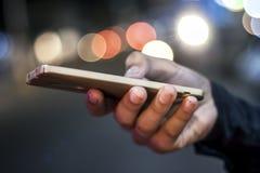 Мобильный телефон в руке на ноче Стоковые Изображения