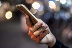 Мобильный телефон в руке на ноче Стоковая Фотография