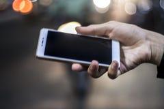 Мобильный телефон в руке на ноче Стоковые Фотографии RF