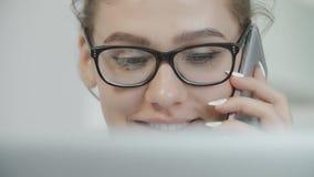 Мобильный телефон девочка-подростка говоря, используя компьтер-книжку, беседуя в социальных сетях при тетрадь, усмехаясь акции видеоматериалы