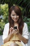 мобильный телефон девушки счастливый используя Стоковые Изображения