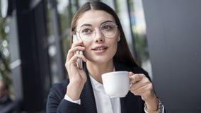 Мобильный телефон молодой женщины говоря и выпивая кофе Стоковое Изображение RF